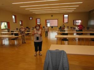 Senioren-Single-Tanz. Die Leiterin, Frau Robert mit Händedesinfektionsmittel